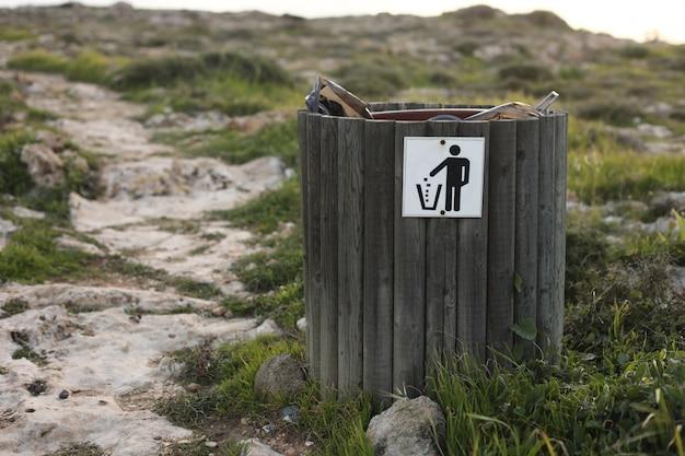 Drewniany Kosz Na śmieci Lub śmieci Z Butelką, Puszką Piwa I Widocznymi Odpadami Organicznymi, Pokazującymi Zanieczyszczenia Na Obszarach Przybrzeżnych W Pobliżu Morza Premium Zdjęcia