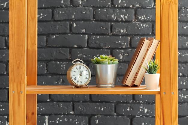 Drewniany regał z książkami i innymi rzeczami na czarnym murem Premium Zdjęcia