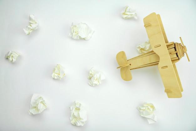 Drewniany samolot z papierową piłką zamiast białych chmur na białego papieru tle Premium Zdjęcia