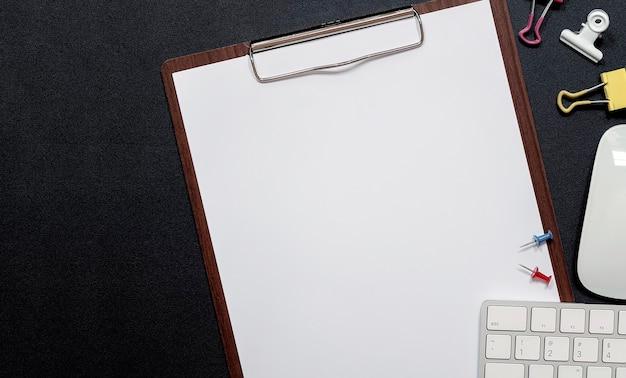 Drewniany Schowek Z Pustą Makietą Papieru I Białą Klawiaturą Komputerową Na Czarnej Skórze Premium Zdjęcia
