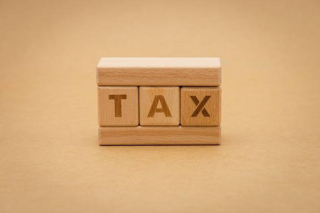 Drewniany słowo podatku pozycja na tle odizolowywa. za pomocą koncepcji biznesowej tła Premium Zdjęcia