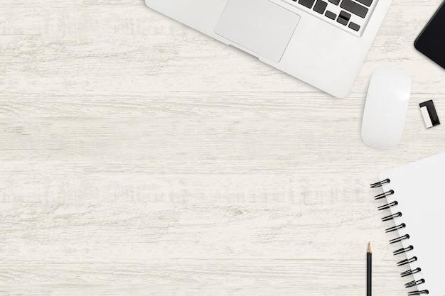 Drewniany stół biurowy z laptopem i artykułami biurowymi. widok z góry przestrzeni roboczej. Premium Zdjęcia