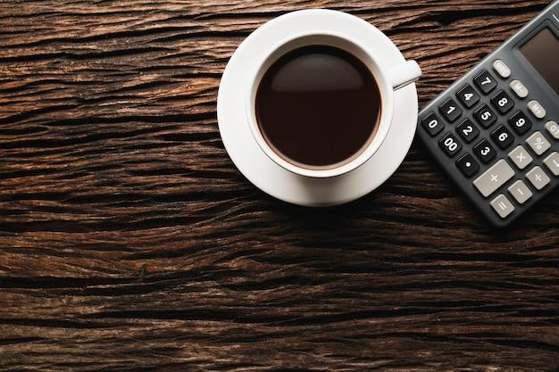 Drewniany Stół Drewniane Biurko Z Kawą I Kalkulatorem. Widok Z Góry Filiżanki Kawy Na Podłoże Drewniane Z Miejsca Na Kopię. Premium Zdjęcia