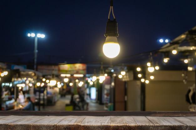 Drewniany Stół Przed Dekoracyjne światła Sznurka Na Zewnątrz Wiszące Na Post Energii Elektrycznej Z Ludźmi Rozmycia. Premium Zdjęcia