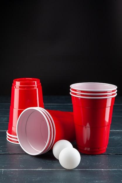 Drewniany stół z czerwonymi filiżankami i piłką do piwa Premium Zdjęcia
