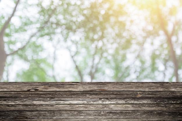 Drewniany Stołowy Przedpole Z Plamy Zieleni Lasowym Tłem Dla Pokaz Natury Produktów Premium Zdjęcia