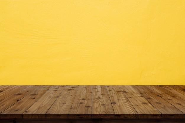 Drewniany Stołowy Wierzchołek Na Kolor żółty ściany Tle. Premium Zdjęcia