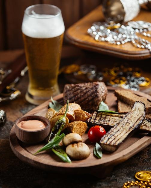 Drewniany talerz steku wołowego z grillowanym bakłażanem, ziemniakami, grzybami i sosem Darmowe Zdjęcia