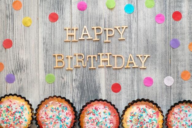 """Drewniany Tekst """"happy Birthday"""" Z Konfetti Papierowymi I Małymi Ciastkami Papugowymi Z Posypanym Cukrem Kolorowym Premium Zdjęcia"""