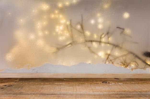 Drewno stół blisko banku śnieg, rośliny gałązka i czarodziejscy światła Darmowe Zdjęcia