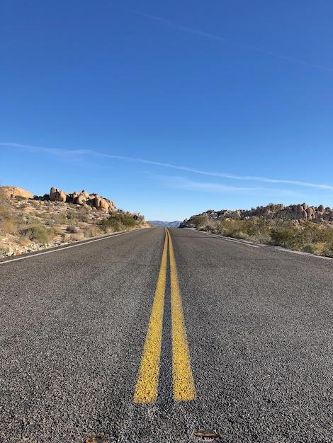 Droga Asfaltowa Z żółtymi Liniami Pod Jasnym, Błękitnym Niebem Darmowe Zdjęcia