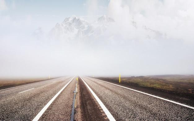 Droga I Ośnieżone Góry, Widok Z Boku. Panoramiczny Krajobraz Premium Zdjęcia