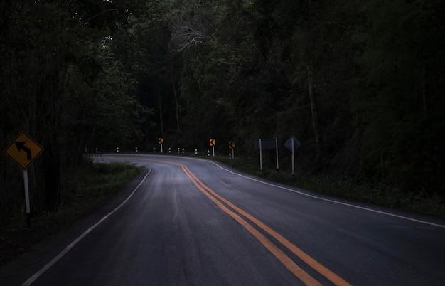Droga Na Ciemnym Widoku Na Górskiej Drodze Wśród Zielonych Drzew Leśnych - Zakręt Asfaltowa Droga Samotny Straszny W Nocy Premium Zdjęcia