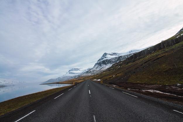 Droga Otoczona Przez Rzekę I Wzgórza Pokryte śniegiem I Trawą Pod Zachmurzonym Niebem W Islandii Darmowe Zdjęcia