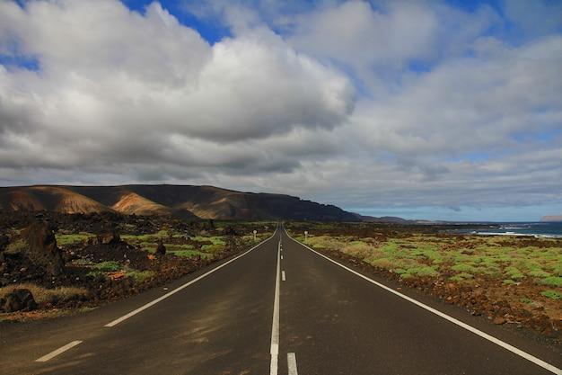Droga Pośrodku Trawiastego Pola Z Górą W Oddali Pod Chmurnym Niebem Darmowe Zdjęcia