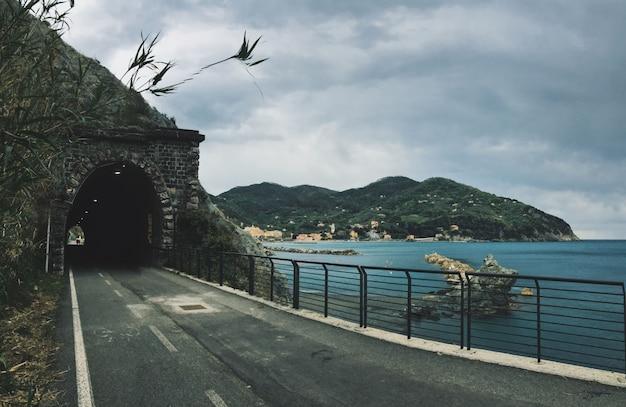 Droga W Kierunku Tunelu W Górze Blisko Morza Z Górami Darmowe Zdjęcia
