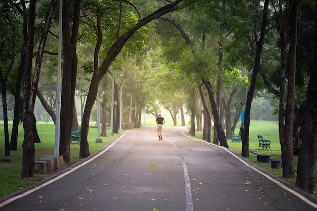 Droga w parku w bangkoku zacienionych zielonych drzew. gdzie ludzie przychodzą na relaks i ćwiczenia. Premium Zdjęcia