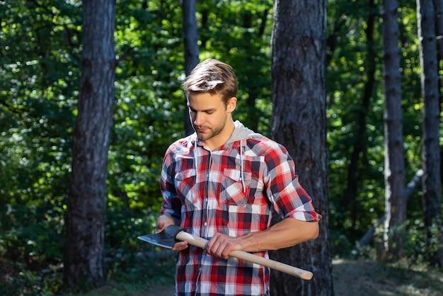 Drwal Stojący Z Siekierą Na Tle Lasu. Wylesianie Jest Główną Przyczyną Powstawania Ziemi Premium Zdjęcia
