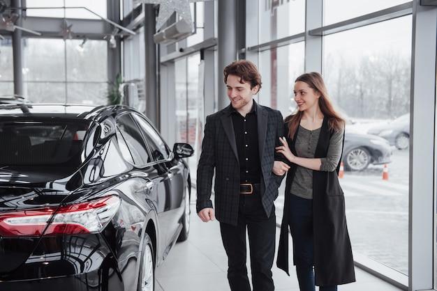 Dumni właściciele. piękny młody szczęśliwy pary przytulenie stoi blisko ich niedawno kupionego samochodu ono uśmiecha się radośnie pokazuje samochodowych kluczy copyspace miłości rodzinnej związku stylu życia kupienia konsumeryzm Premium Zdjęcia