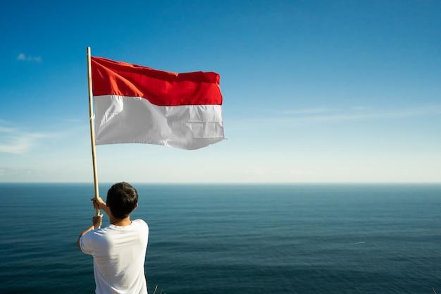 Dumny Indonezyjczyk Na Plaży, Podnosząc Biało-czerwoną Flagę Indonezji Premium Zdjęcia