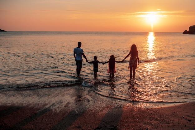 Duża Czteroosobowa Rodzina Cieszy Się Zachodem Słońca. Widok Z Tyłu Premium Zdjęcia