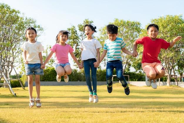 Duża Grupa Szczęśliwy Azjatycki Uśmiechający Się Przedszkole żartuje Przyjaciół Trzymając Się Za Ręce, Grając I Skacząc Razem W Słoneczny Dzień W Ubranie W Parku Miejskim. Premium Zdjęcia