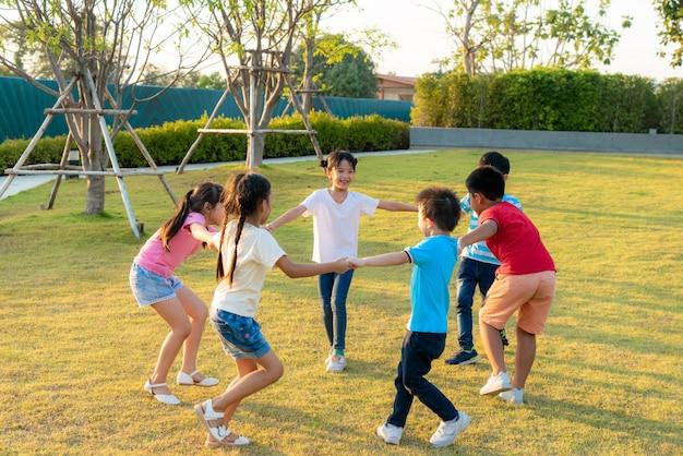 Duża Grupa Szczęśliwych Azjatyckich Uśmiechniętych Przedszkolaków żartuje Przyjaciół, Trzymając Się Za Ręce, Grając I Tańcząc, Grając W Kółko I Stojąc W Okręgu W Parku Na Zielonej Trawie W Słoneczny Letni Dzień. Premium Zdjęcia