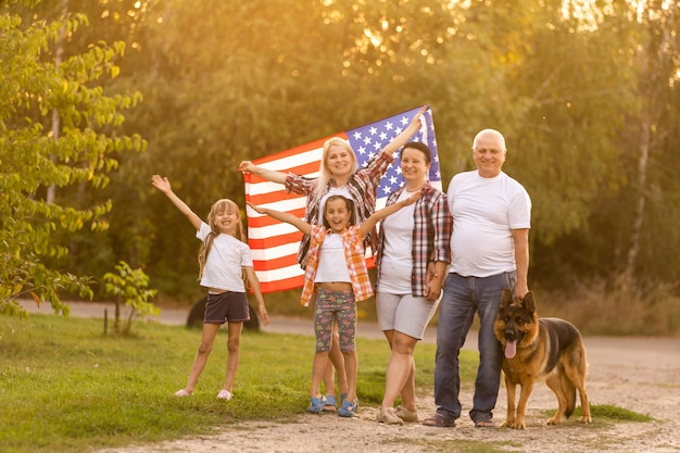 Duża Rodzina Spaceruje Po Amerykańskich Flagach. Widok Z Przodu, Amerykańscy Patrioci Na łące W Parku. Premium Zdjęcia