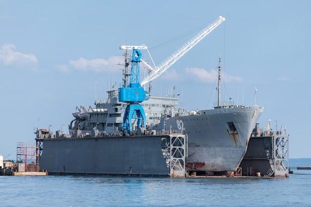 Duże żelazne Statki Marynarki Wojennej W Stoczni Do Naprawy. Duży Dźwig W Stoczni. Port Morza Niebieskiego Premium Zdjęcia