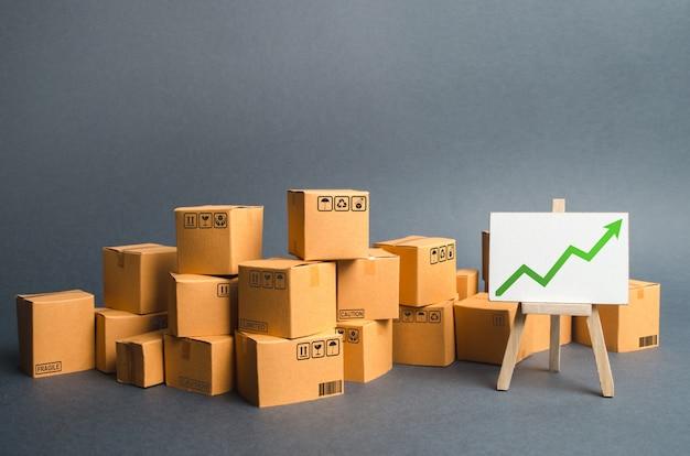Dużo kartonów i stojak z zieloną strzałką w górę. tempo wzrostu produkcji towarów Premium Zdjęcia