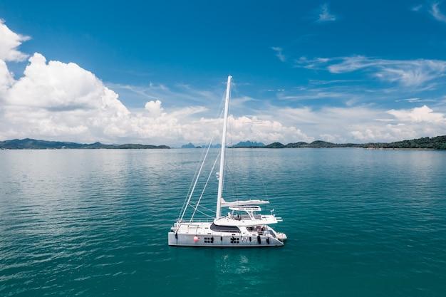 Duży biały jacht pływający w ciepłym lazurowym oceanie. pływające statki. czas odpoczynku. drogie wakacje. zdjęcie z kwadrokoptera. tropikalny charakter. bogate bogactwo. Premium Zdjęcia