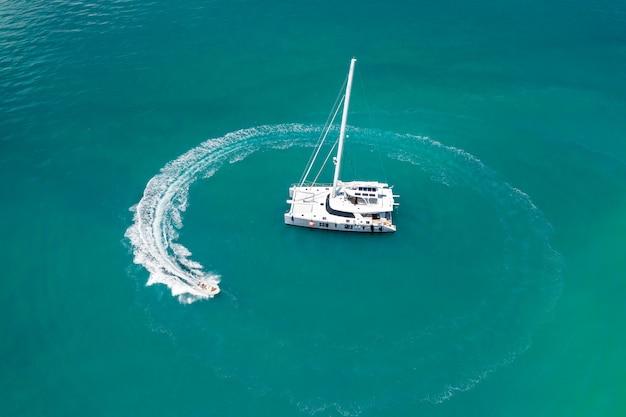 Duży biały jacht żeglujący po ciepłym lazurowym oceanie, obok którego dryfuje mała łódka, pozostawiając za sobą fale. pływające statki. czas odpoczynku. zdjęcie z góry. drogie wakacje. zdjęcie z kwadrokoptera. Premium Zdjęcia