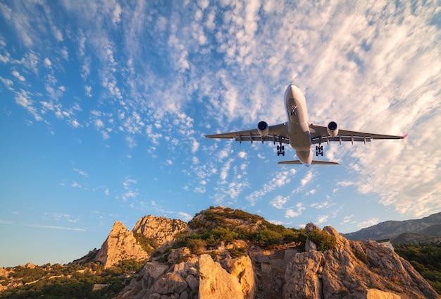 Duży Biały Samolot Leci Nad Skałami O Wschodzie Słońca. Premium Zdjęcia