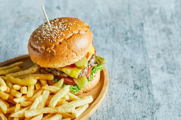Duży Burger Ze Smażonym Ziemniakiem Na Drewnianym Talerzu Na Marmurowym Stole. Darmowe Zdjęcia
