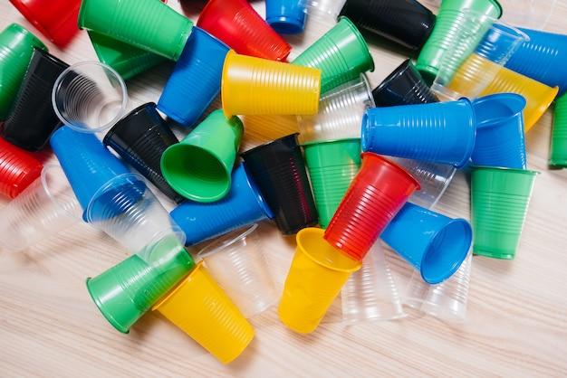 Duży Stos Kolorowych Plastikowych Kubków Rozsypanych Na Podłodze. Zanieczyszczenie środowiska Odpadami Ludzkimi. Premium Zdjęcia