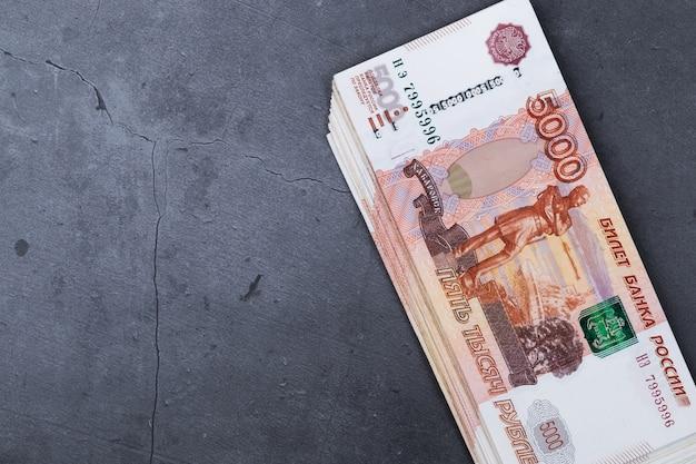 Duży stos rosyjskich banknotów pieniędzy o wartości pięciu tysięcy rubli leżących na szarej cementu. Premium Zdjęcia