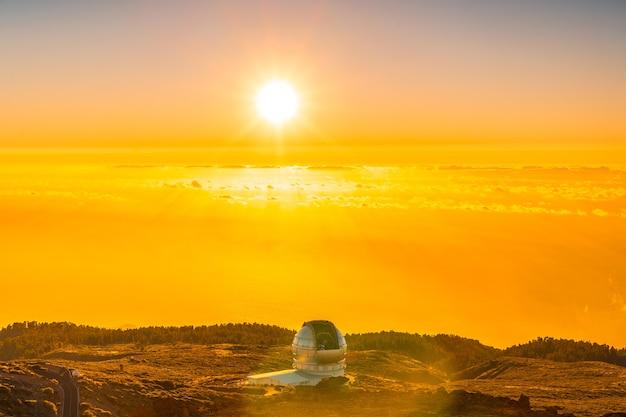 Duży Teleskop Kanaryjski Zwany Grantecan Optico Del Roque De Los Muchachos Na Caldera De Taburiente W Pięknym Pomarańczowym Zachodzie Słońca, La Palma, Wyspy Kanaryjskie. Hiszpania Premium Zdjęcia
