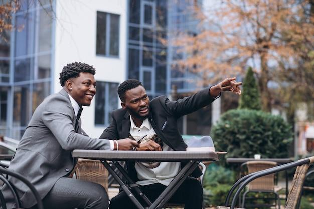 Dwa afrykański biznesmena obsiadanie na zewnątrz kawiarni Darmowe Zdjęcia