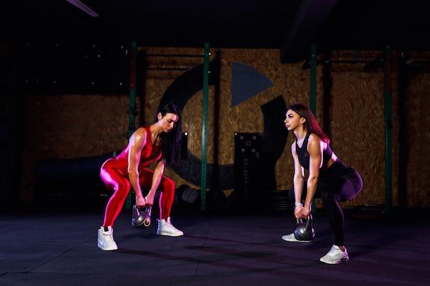 Dwa atrakcyjne dopasowanie sportowca kobiet wykonujących huśtawka dzwon czajnik w siłowni Premium Zdjęcia