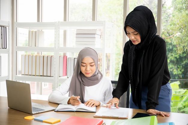 Dwa Azjatyckich Muzułmańskich Bizneswomanów Opowiada Wpólnie I Pracuje W Biurze Premium Zdjęcia