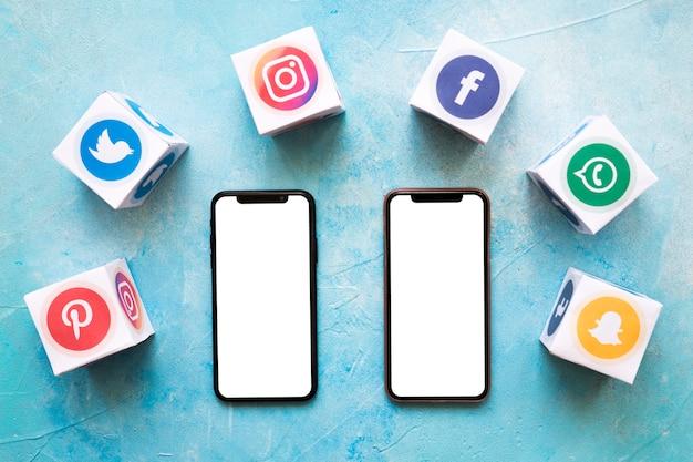 Dwa Białe Puste Telefon Otoczony Z Social Networking Bloków Na ścianie Malowane Premium Zdjęcia