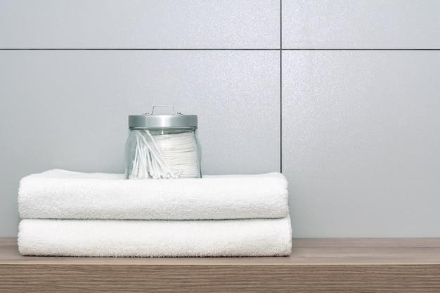 Dwa Białe Ręczniki Starannie Złożone Leżą Na Drewnianej Półce, Na Której Stoi Puszka Z Wacikami I Nausznikami Na Płytce Ceramicznej. Premium Zdjęcia