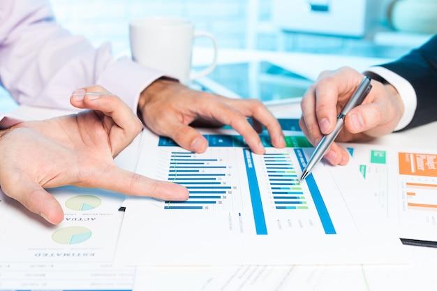 Dwa biznesmen ręki dyskutuje niektóre plany biznesowych na spotkaniu Premium Zdjęcia