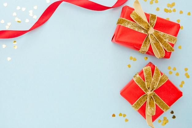 Dwa Czerwone Pudełka Na Prezenty Ze Złotą Błyszczącą Wstążką I Złotymi Konfetti. Premium Zdjęcia