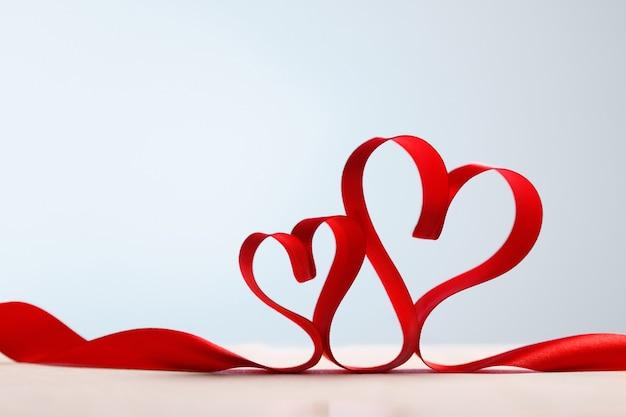 Dwa Czerwone Serca Wstążki. Walentynki Kartkę Z życzeniami, Miejsce Na Kopię. Premium Zdjęcia