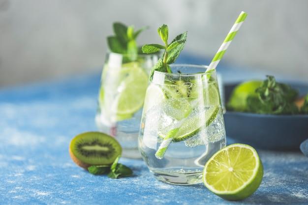 Dwa Detoksykacyjne Koktajle Z Wodą Lub Martini Z Kiwi, Limonką, Lodem I Miętą Premium Zdjęcia