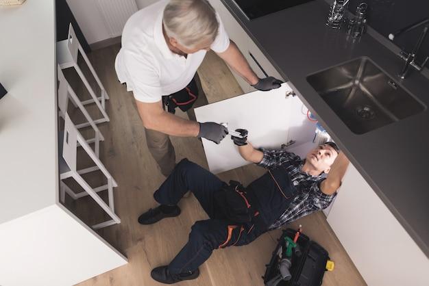 Dwa dobre hydraulików w kuchni naprawa zlewozmywaka. Premium Zdjęcia