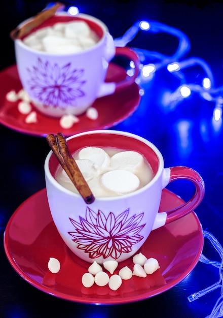 Dwa filiżanek gorąca biała czekolada z marshmallow na czerwień talerzu. czarny i oświetlenie. tradycyjny świąteczny napój. Premium Zdjęcia