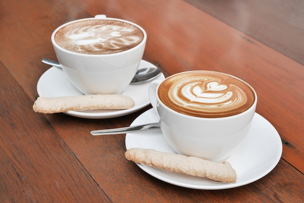Dwa Filiżanki Latte Sztuki Kawa W Białej Filiżance Na Drewnianym Tle Premium Zdjęcia
