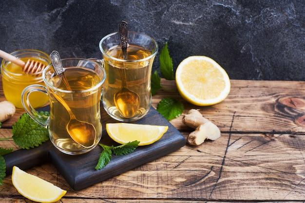 Dwa Filiżanki Naturalnej Ziołowej Herbaty Imbirowej Cytryny Mennica I Miód Na Drewnianym Tle. Skopiuj Miejsce Premium Zdjęcia